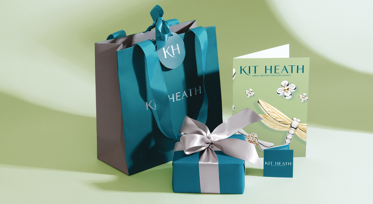 Luxury gift wrap presentation box and bag with branded premium teal wrap and silver satin ribbon.